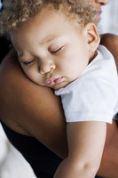 Boy sleeping on his mother s shoulder
