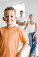 Boy smiling at the camera with his parents in the background