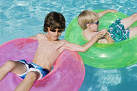 Boys on float tubes in swimming pool
