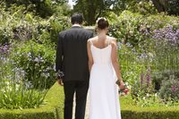 Bride and groom walking in garden back view