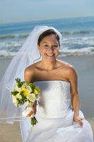 Bride with bouquet on beach smiling  portrait