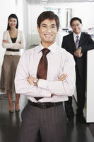 Business man standing in front of colleagues in office portrait