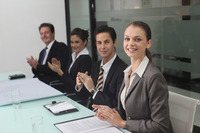Business people clapping hands in conference room
