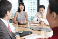 Business people sitting round table in conference room