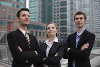 Business people standing outdoors with arms crossed