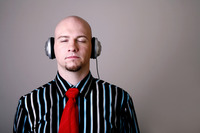 Popular : Businessman closing his eyes while listening to music on the headphones