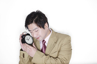 Businessman holding an alarm clock while sleeping
