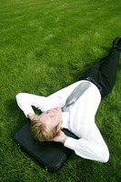 Businessman lying on the field with his head on the briefcase