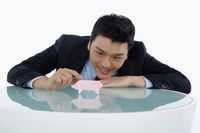 Popular : Businessman playing with a paper pig