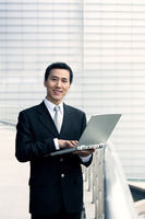 Businessman smiling at the camera while using laptop