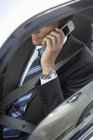 Businessman using mobile phone in car mid section elevated view