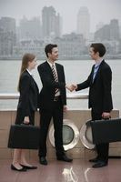 Businessmen shaking hands with businesswoman watching at the side