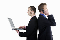 Businessmen talking on the cell phone and using laptop