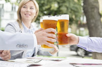 Businesspeople toasting beer glasses at outdoor restaurant