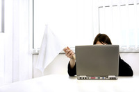 Businesswoman holding a white flag while using laptop