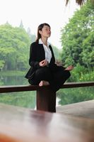 Businesswoman meditating on bench