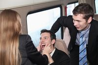 Businesswoman pinching businessman s cheek  colleague looking on