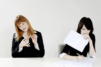 Popular : Businesswoman shaping her fingernail while her colleague is busy doing her work