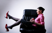 Businesswoman sitting on the chair playing with laptop