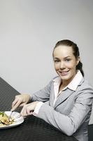 Businesswoman smiling at the camera while enjoying her meal