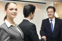 Businesswoman smiling  businessmen shaking hands in the background