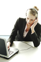 Businesswoman using headset and laptop