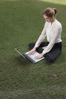 Businesswoman using laptop on the field