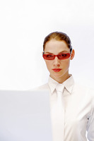 Businesswoman wearing a funky red sunglass while using the laptop