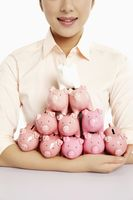 Businesswoman with an armful of piggy banks