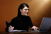 Businesswoman writing while using laptop