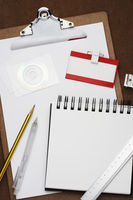 Clipboard notepad pencil and other office equipment arranged in studio