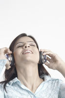 Close-up of a young woman listening to music wearing headphones