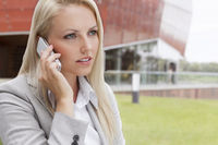 Close-up of young businesswoman conversing on mobile phone against office building