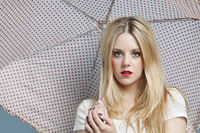 Close-up portrait of young woman holding polka dots umbrella