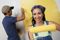 Couple painting interior wall yellow
