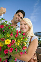 Couple standing in plant nursery holding hanging plant portrait low angle view