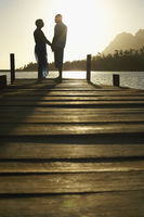 Couple standing on dock by lake holding hands side view