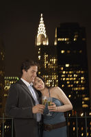 Couple toasting with champagne against new york night skyline