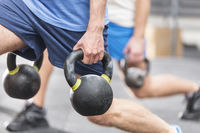 Cropped image of men lifting kettlebells at crossfit gym
