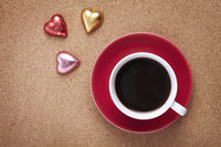 Cup of coffee with heart shaped chocolates