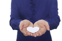 Cupped hands with a paper heart