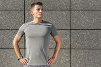 Popular : Determined jogger standing against tiled wall outdoors