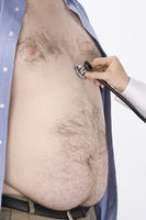 Doctor hand with stethoscope on overweight man s heart mid section