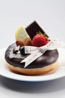 Donut decorated with ribbon  fruit garnishing and almond