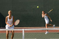 Doubles player hitting tennis ball with forehand team-mate standing at net