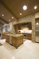Exposed stone kitchen surround with spotlights on wooden ceiling