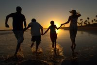Family running through sea holding hands at sunset back view silhouette