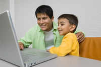 Father and son at desk using laptop close up
