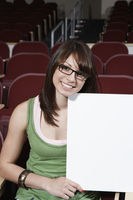 Female student holding blank board in lecture theatre portrait