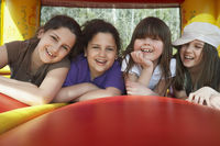 Popular : Four girls  7-12  lying in row in bouncy castle laughing portrait